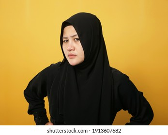 Portrait of cynical Asian muslim woman with suspicious expression looking and starring, mistrust misdoubt concept