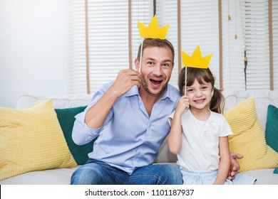 Portrait of dad and child daughter are playing and having fun together. Beautiful funny girl and daddy have crowns on sticks. Fun love family lifestyle single dad love father's day holiday concept
