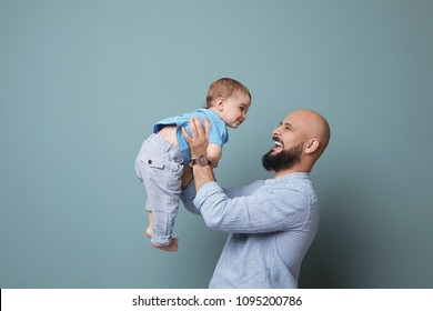 Portrait of dad and his little son on color background