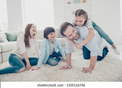 Portrait of daddy standing on knees carrying on back daughter mom and son sitting on the floor laughing enjoying game. Free-time daydream domestic lifestyle upbringing care concept