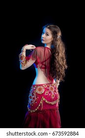 portrait dancer brunette girl with long hair in red oriental costume posing and dancing on black background in studio