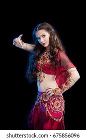 Portrait of a Dancer brunette girl with long hair in red oriental costume posing and dancing on black background in studio