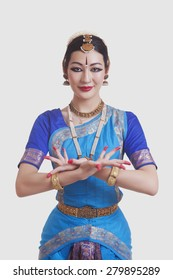 Portrait of dancer gesturing while performing Bharatanatyam against white background