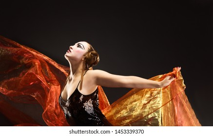 Portrait of a dancing young woman with flying fabric over dark gray background.
