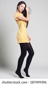 Portrait of a dancing young woman in yellow sweater. fashion concept and style. Spring clothes.