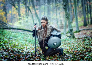 Portrait of dangerous, beautiful scandinavian viking woman warrior fur collar and specific makeup holding ax and shield, ready to attack and defend her territory.
