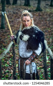 Portrait of dangerous, beautiful scandinavian viking woman warrior fur collar and specific makeup rising ax above head, ready to attack and defend the bridge and territory.