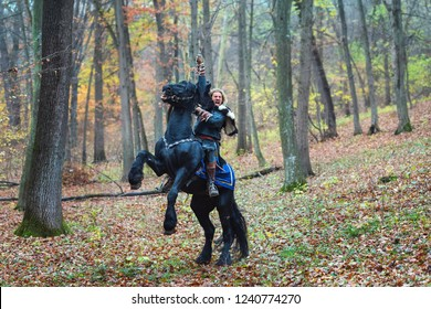 Portrait of dangerous, scandinavian viking man riding black horse in forest holding sword attacking. Northern warrior male in traditional clothes with fur collar, ready to attack in battle.