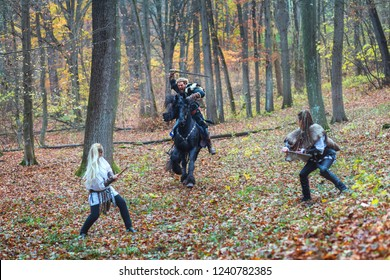Portrait of dangerous, scandinavian viking man riding black horse in forest holding sword attacking two Viking warrior women in forest. Selective focus