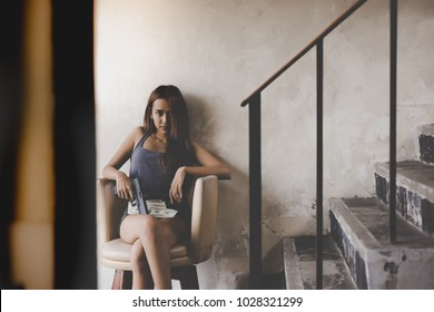 Portrait dangerous woman: Attractive young asian girl is looking something. Charming beautiful woman holds a gun. She sells illegal things or drugs. Asia girl sits on armchair in retro building.