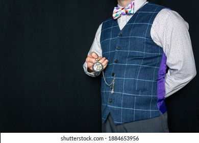 Portrait of Dapper Man in Tweed Vest and Colorful Bow Tie Holding Pocket Watch. Vintage Fashion and Style. Elegant Gentleman. Clothing Model