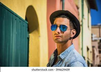 Portrait of dark haired young man in blue mirrored sunglasses and black hat. Cityscape on background, with colorful houses in Italy