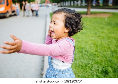 Portrait of dark skinned active hysteric hispanic or mexican toddler girl crying and stretching out her hand. Child dressed in casual clothing: blue denim sarafan, pink shirt. Summer time shot