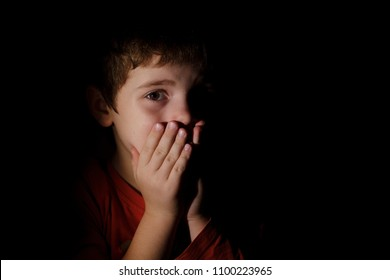 Portrait in the dark of a young boy of 7 years scared and upset hands on the mouth in the dark backround in the profile