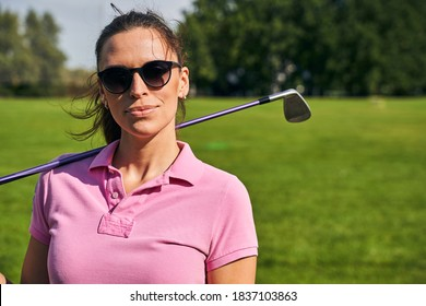 Portrait of a dark-haired female athlete in a polo shirt and trendy sunglasses looking ahead