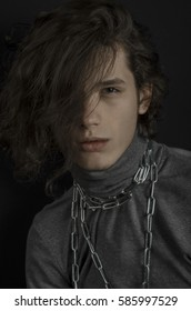 Portrait of a dark-haired guy with a chain around his neck