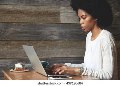 Portrait of dark-skinned female freelancer typing a message via email, using laptop computer for distant work while sitting at a coffee shop, looking at the screen with serious concentrated expression