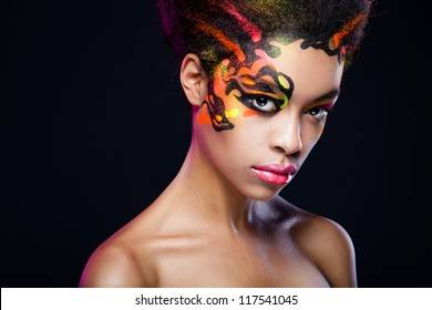 portrait of the dark-skinned girl with unusual make-up on dark background