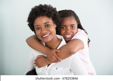 Portrait Of A Daughter Embracing Her Mother From Behind Against White Background