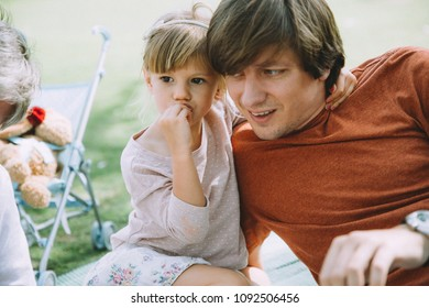 Portrait of daughter and father looking in one direction sitting on the grass