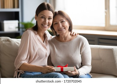 Portrait daughter hugging and congratulating older mother with birthday, mothers day or 8 march, happy young woman and mature mom holding gift box, looking at camera, sitting on couch at home