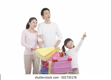 Portrait of daughter with parents ,pushing shopping cart,looking away