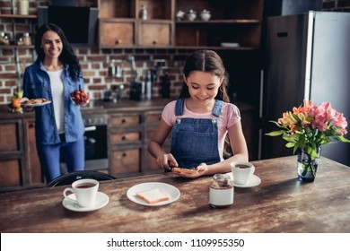 portrait of daughter spreading toast with chocolate paste, helping mother in preparing breakfast in the kitchen