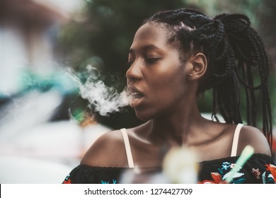 Portrait of a dazzling African girl with braids sitting in a street cafe and exhaling smoke from the hookah; young black female outdoors in a bar plays with the vapor from an electronic cigarette