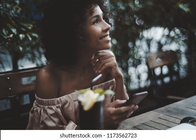 Portrait of dazzling African-American girl sitting in cafe and dreaming about something while holding the smartphone in hand; side view of curly black woman holding the cellphone in a bar outdoors