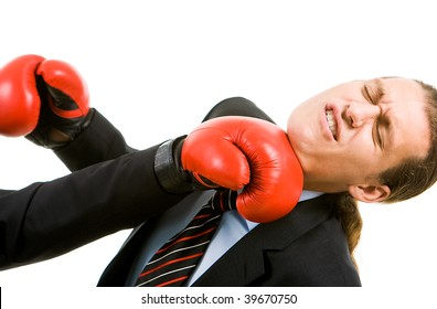 Portrait of defeated businessman in boxing gloves being hit by opponent