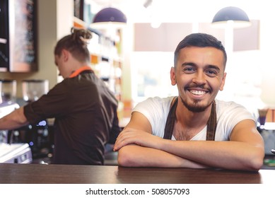 portrait of a delighted guy in apron smiling at the camera while standing in the cafeteria