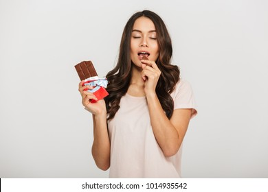 Portrait of a delighted young asian woman eating chocolate bar isolated over white background