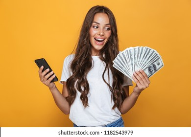 Portrait of a delighted young girl with long brunette hair standing over yellow background, holding money banknotes, using mobile phone
