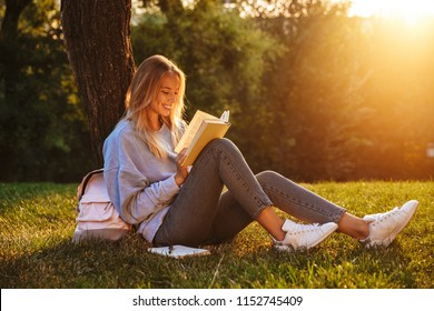 Portrait of a delighted young girl sitting on a grass at the park, reading a book, taking notes