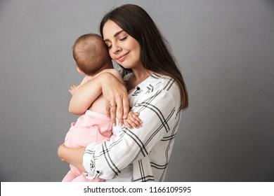 Portrait of a delighted young mother holding her little baby girl over gray background