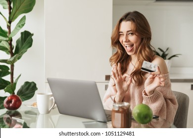 Portrait of a delighted young woman holding credit card while sitting with laptop computer at the table at home