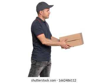 Portrait of Delivery man in cap holding big cardboard box. Handsome man looking away. Courier isolated on white background. Side view - profile.