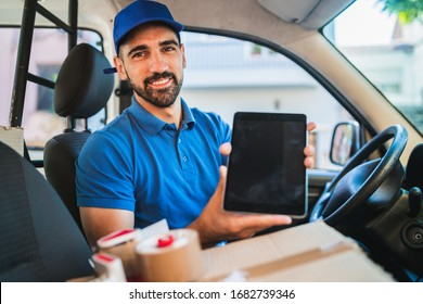 Portrait of a delivery man driver using digital tablet while sitting in van. Delivery service and shipping concept.
