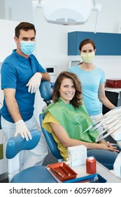 Portrait of dental team and patient in dentist's office.