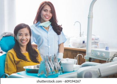 portrait of Dentist smiling with female patient in dental clinic