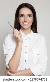 Portrait of dentist smiling woman holding toothbrush in hand