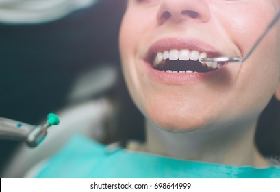 Portrait of a dentist who treats teeth of young woman patient.