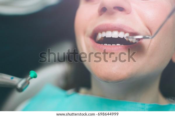 Porträt eines Zahnarztes, der Zähne eines jungen weiblichen Patienten behandelt.