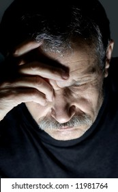 Portrait of depressed aged man thinking and holding his head by hand