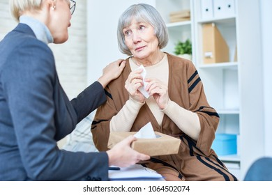 Portrait of depressed elderly woman confining in female psychologist during therapy session, copy space