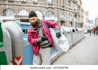 Portrait of depressed homless beggar standing with bag near the trash containers in the city