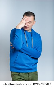 portrait of a depressed man, dressed in a blue hoodie, isolated on a gray background