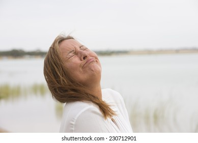 Portrait depressed mature woman with sad, stressed, painful facial expression, crying with closed eyes outdoor, blurred background and copy space.