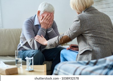 Portrait of depressed senior man crying during therapy session with female psychiatrist trying to console him