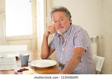 Portrait of depressed senior old man with grey hair reading the newspaper while having breakfast and drinking a coffee in old age retirement concept.